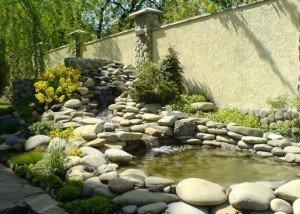 Водоем в саду из натурального камня и полированной гальки